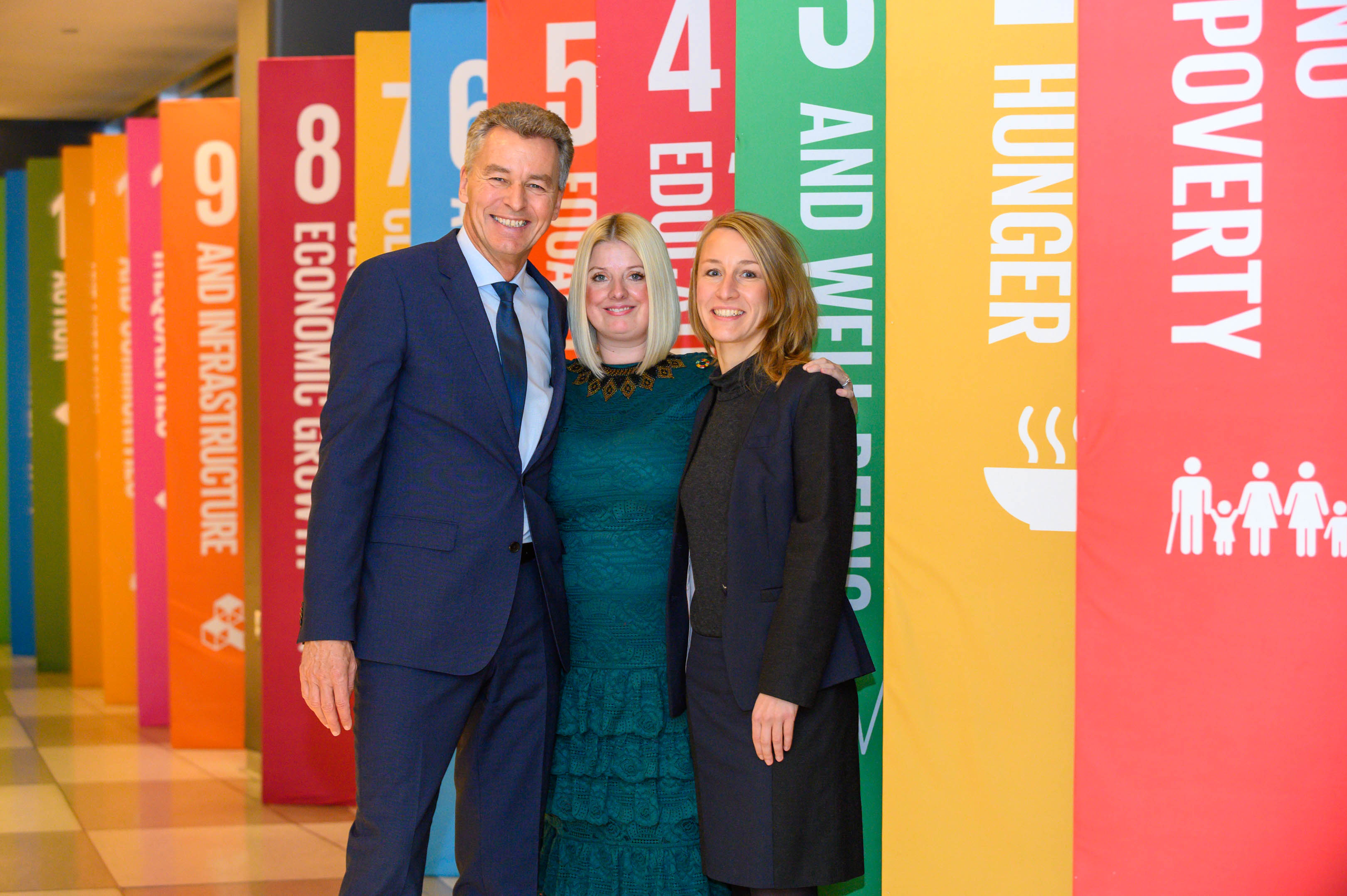 Conscious Fashion Campaign founder Kerry Bannigan (center) stands with Detlef Braun (left) and Lilliffer Seiler (right) of Messe Frankfurt beside a series of panels outlining the United Nations' Sustainable Development Goals (Photography courtesy of Rich Dodge for Messe Frankfurt)