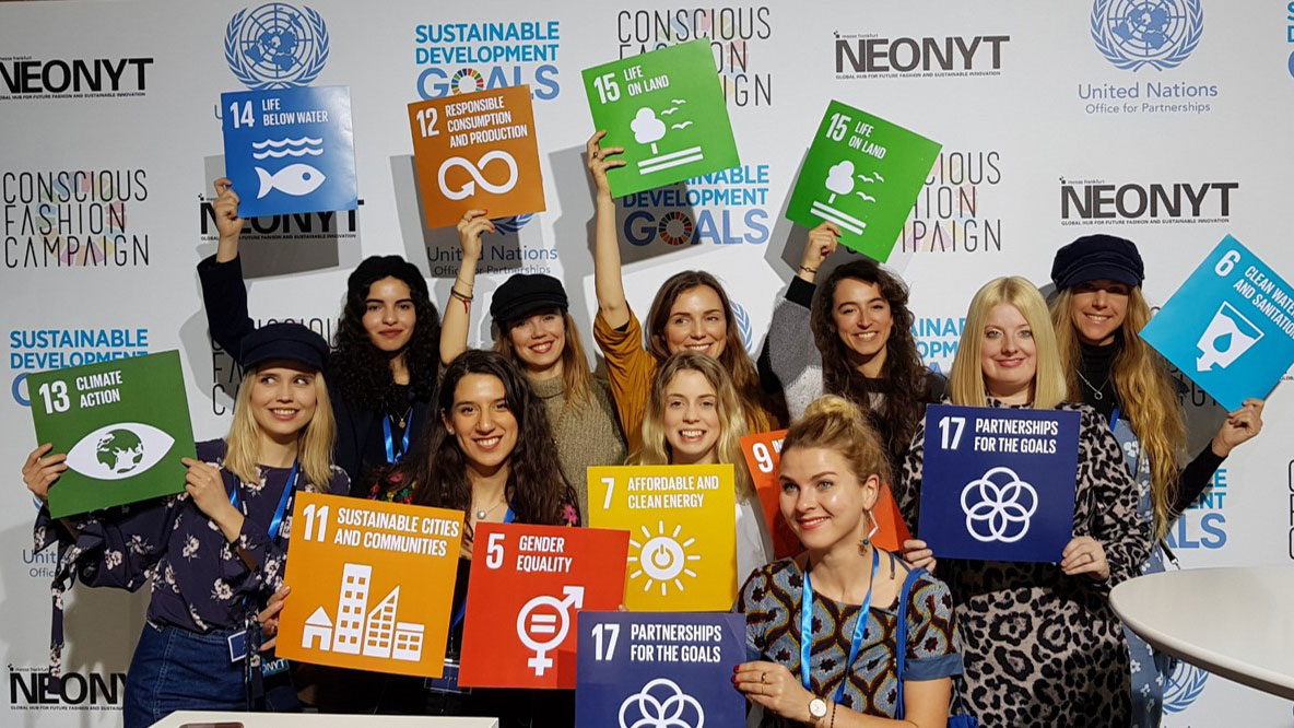 Kerry Bannigan (right) stands with a group of visitors in front of the Sustainable Development Goals presentation during the Neonyt tradeshow in July 2019. (Source: Messe Frankfurt, Neonyt)